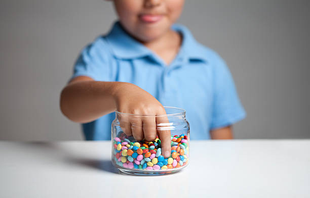 Little boy taking candy from jar Little boy licking his lips while taking candy from the candy jar. temptation stock pictures, royalty-free photos & images