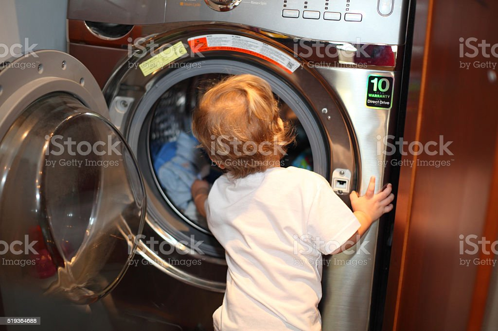 Little boy taking clothes out of a washing machine stock photo