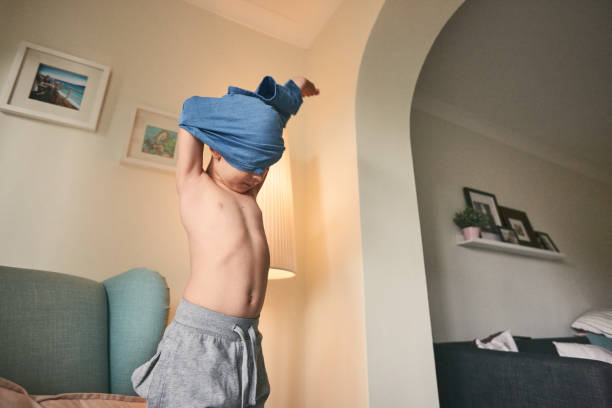 Little boy taking off his tshirt Little boy taking off his tshirt. Preteen boy undressing at home. undressing stock pictures, royalty-free photos & images