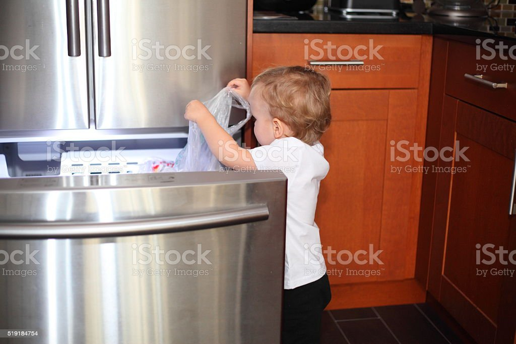 Little boy taking things out of the freezer stock photo