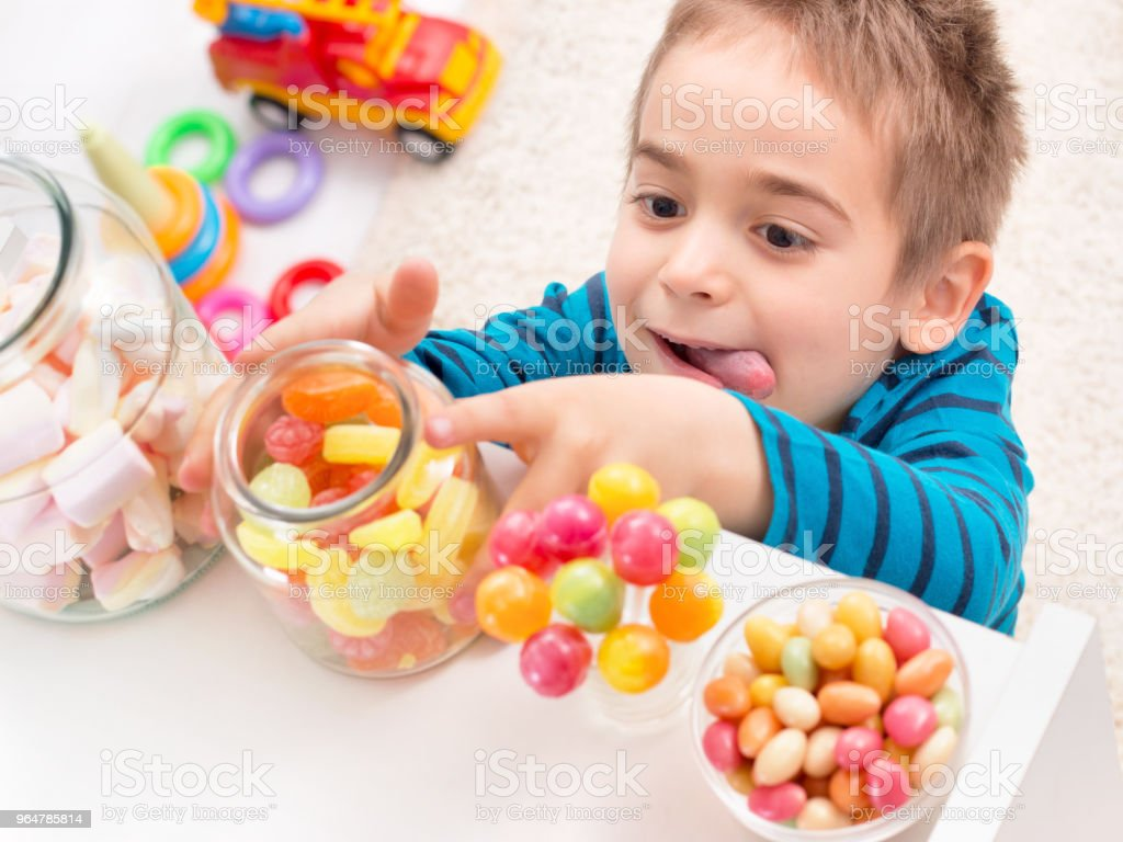 Little boy taking too much candy royalty-free stock photo