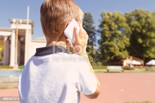Speaking with granny. Back view of little boy talking per mobile phone outside