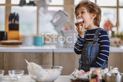 Little Son Tasting Mommy's Muffins on His Birthday in Kitchen
