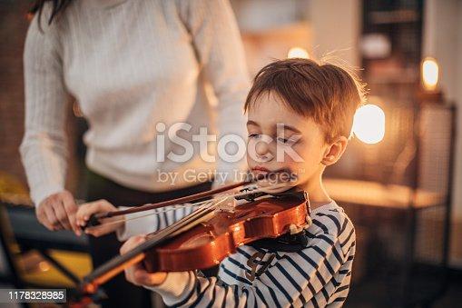 Little boy teaching to play violin