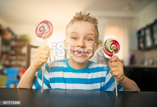 Portrait of a grinning little boy holding two lollipops. The boy's smile is missing couple of teeth, possible because of eating too much candy.