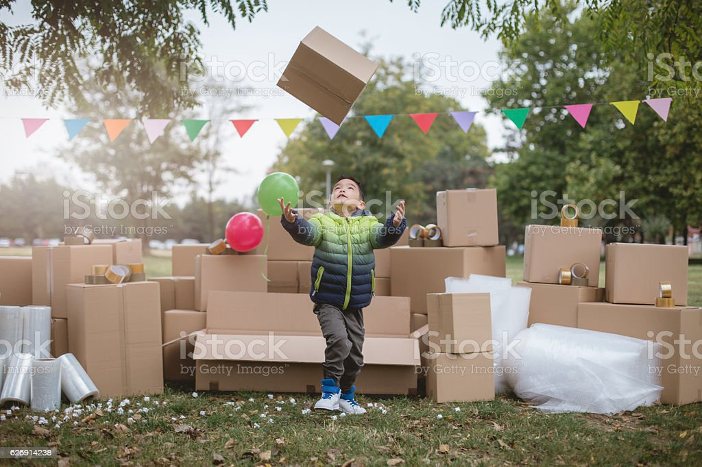 little boy throwing and catching cardboard box stock photo