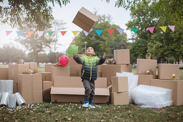 little boy throwing and catching cardboard box - kinder verpackung stock-fotos und bilder
