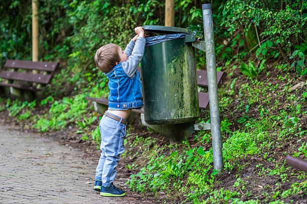 Kleiner Junge in den Müll werfen Müll – Foto