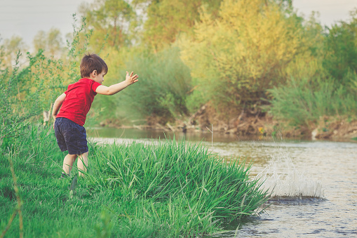 Little boy throws stone ino the river