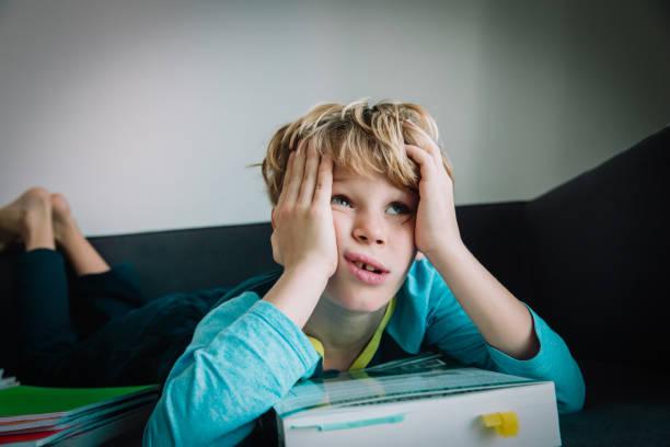 Der kleine Junge, der müde ist, zu lesen, das Kind langweilt sich, Hausaufgaben zu machen – Foto