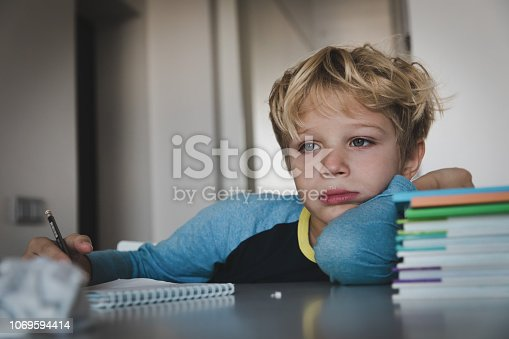 istock little boy tired stressed of reading, doing homework 1069594414