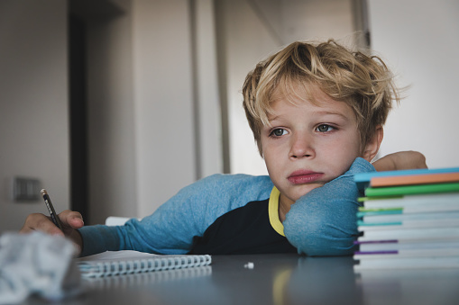 istock little boy tired stressed of reading, doing homework 1069594414