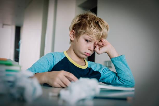 Der kleine Junge müde gestresst des Schreibens, Hausaufgaben machen – Foto