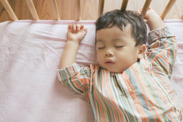 little boy toddler adorably sleeping in his baby cot while wearing traditional malay clothing, ramadan and eid concepts stock photo - playpen stock pictures, royalty-free photos & images