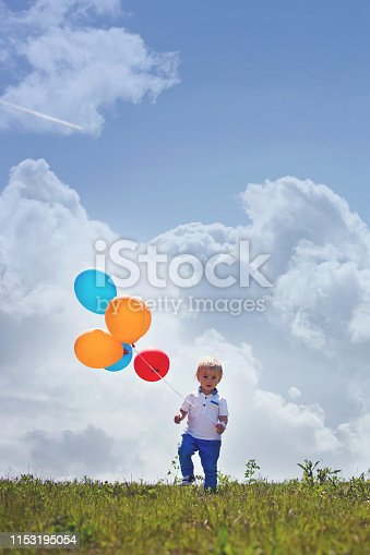 Little boy, toddler, child playing with colorful balloons in the park on kids day, sunny summer afternoon in nature