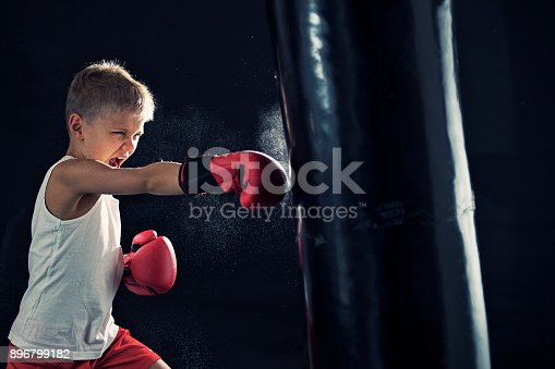 istock Little boy training boxing with punching bag 896799182