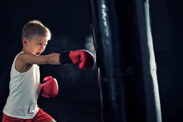 Little boy training boxing with punching bag stock photo