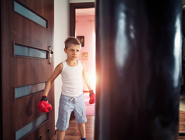 Little boy training with punching bag at home stock photo