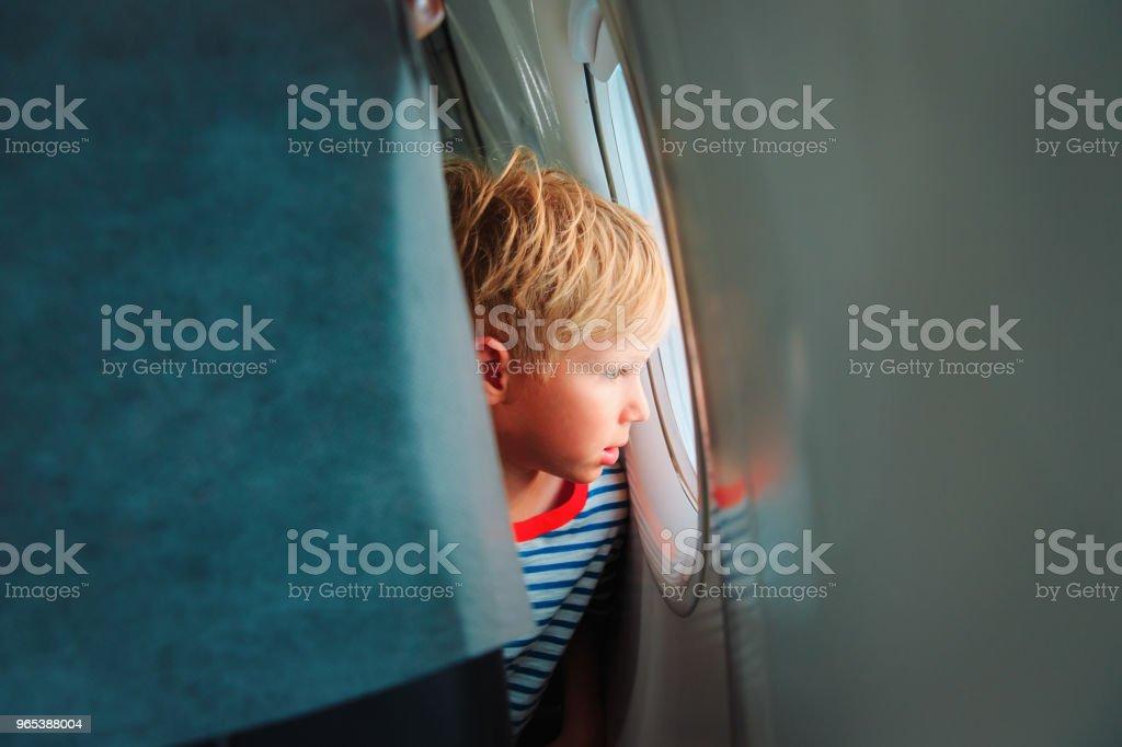 petit garçon de voyage en avion, regardant par la fenêtre - Photo de Attendre libre de droits