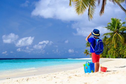 little boy travel on beach with suitcase and binoculars
