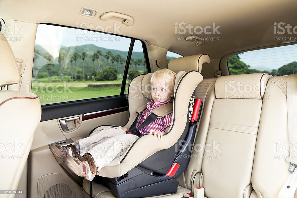 Little Boy Traveling Safely in Car Seat stock photo