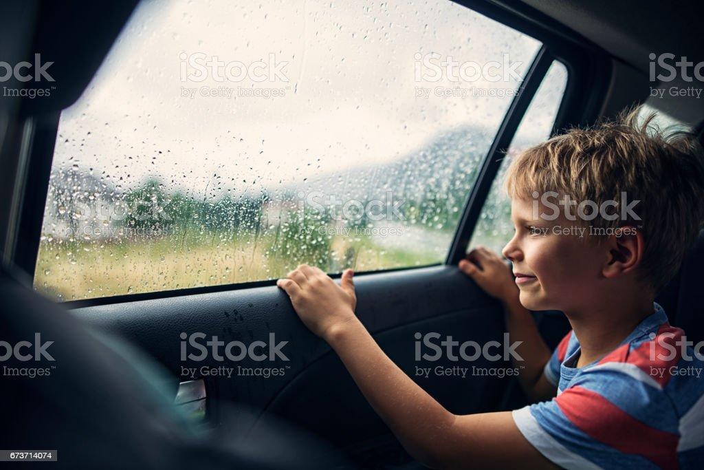 Niño, viajar en coche en un día lluvioso - foto de stock