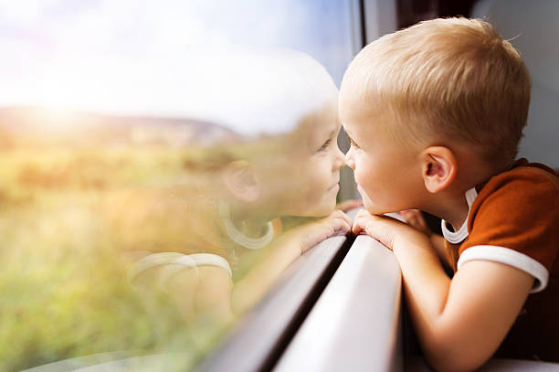 little boy travelling in train - boy looking out window stock pictures, royalty-free photos & images