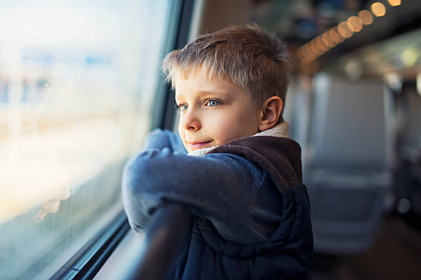 little boy travelling on train - boy looking out window stock pictures, royalty-free photos & images