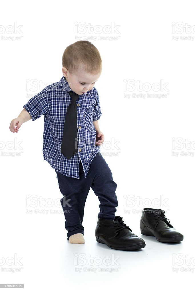little boy trying on father shoes stock photo