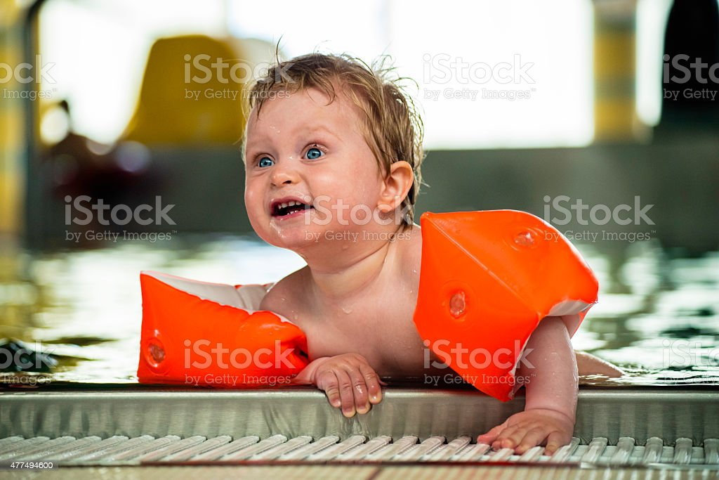Little boy trying to get out of a pool stock photo