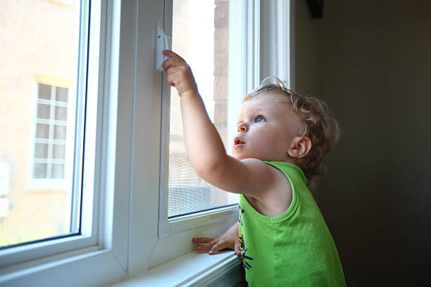 little boy trying to open the window - schulterfreies oberteil stock-fotos und bilder