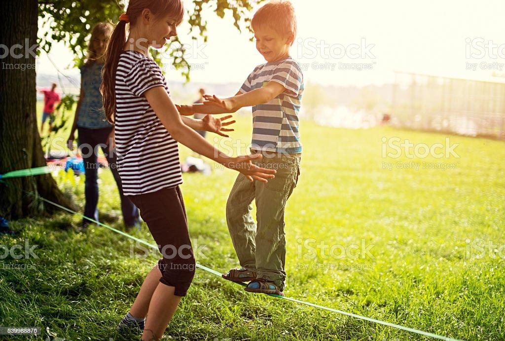 Little boy trying to walk on slackline stock photo