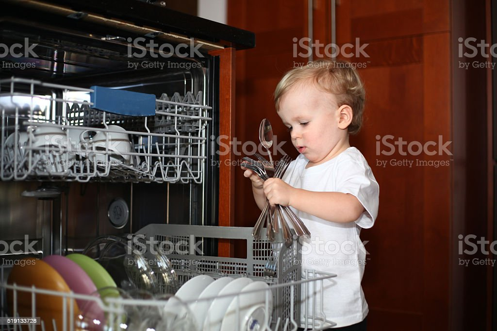 Little boy unloading silverware from the dishwasher stock photo
