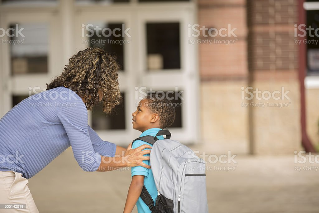 Little boy unsure on his first day of school.  Mother. stock photo