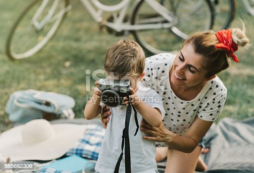 Little boy playing with a vintage camera on a family picnic outdoors.