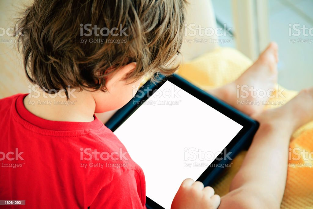 A little boy using a tablet at home royalty-free stock photo