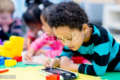 istock Little Boy using a Tablet PC in Preschool 473738116