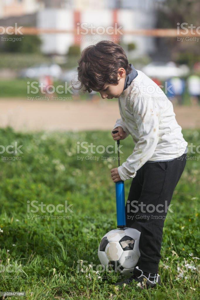 Kleiner Junge mit Fahrradpumpe seinen Soccer Ball Aufpumpen – Foto