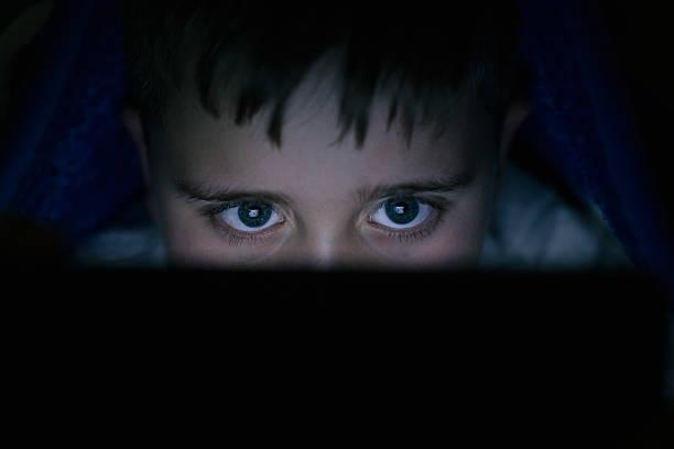 kleine junge mit digitalen tablet im bett - free online game stock-fotos und bilder