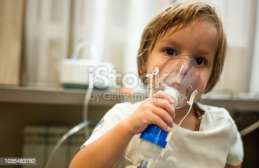 Small kid receiving asthma treatment and using inhaler at home.