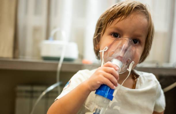 Kleiner Junge mit Vernebler während Therapie inhalieren. – Foto