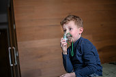 Little boy using nebulizer during inhaling therapy