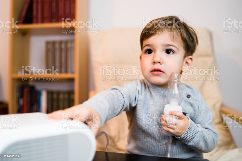 Little Boy Using Steam Inhaler Nebulizer Mask Inhalation At Home