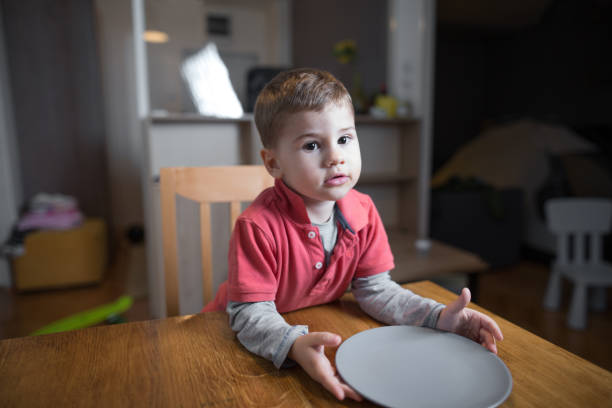 Little boy waiting for his dinner Cute little hungry boy waiting for his dinner hungry stock pictures, royalty-free photos & images