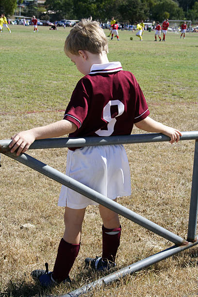 Little boy waiting in reserve to play in soccer game stock photo