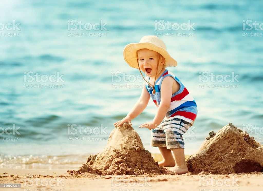 little boy walking at the beach in straw hat stock photo