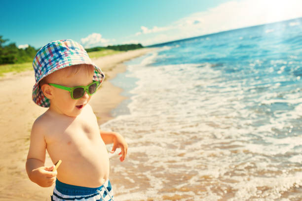little boy walking at the beach in summer hat stock photo