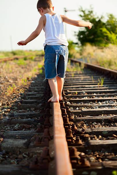 Little boy walking down train track stock photo