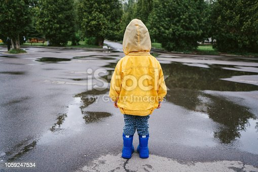 Little boy in yellow raincoat  walking outdoors and jumping on puddle