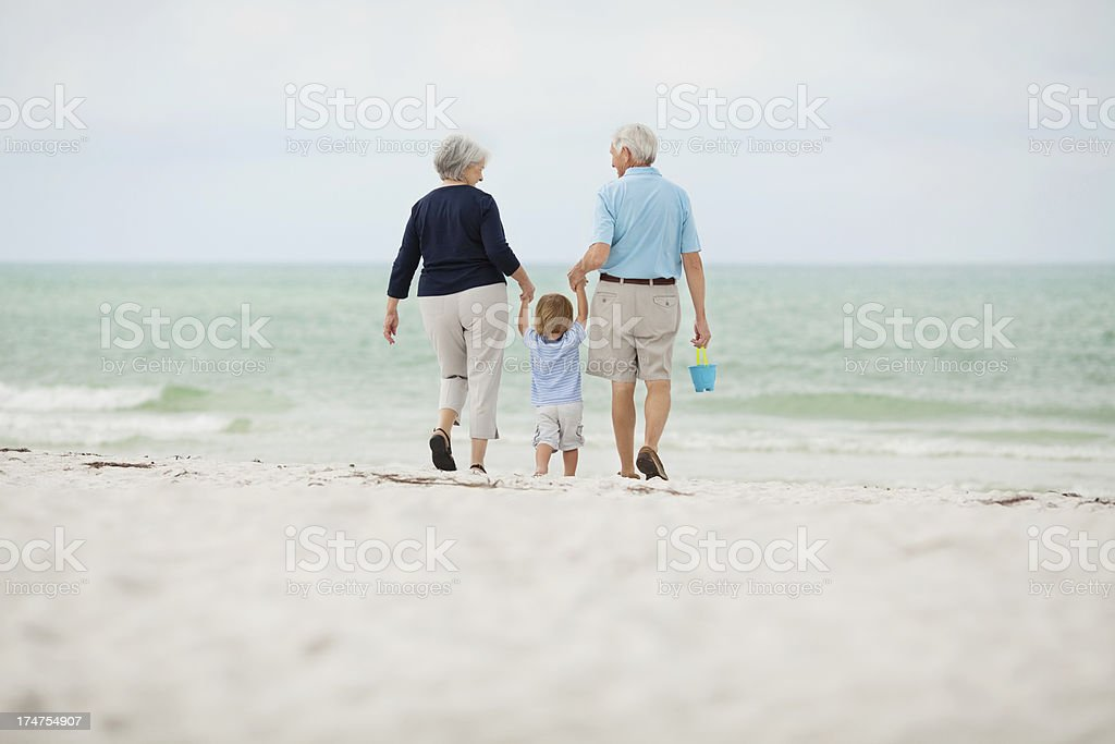 Little Boy Walking With Grandparents At Beach royalty-free stock photo